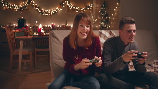 クリスマスの夜にビデオゲームをしている若いカップル。 - control点の映像素材/bロール