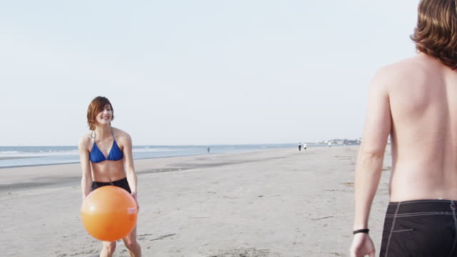 ms slo mo  young couple playing with beach ball at beach / isle of palms, south carolina, usa - bikinioberteil stock-videos und b-roll-filmmaterial