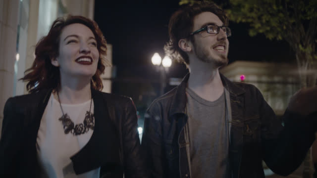 vídeos de stock e filmes b-roll de ms slo mo. young couple point up at buildings exploring city at night. - mostrar