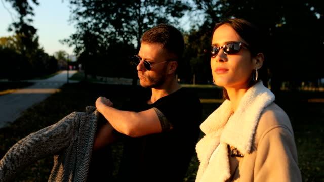 vidéos et rushes de jeune couple posant dans le parc - lunette soleil