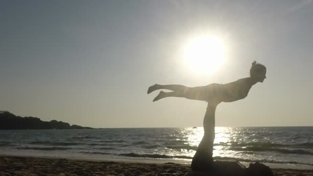 Young couple practice Acro Yoga on the beach - vertical lift part 1