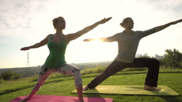 Young couple practice yoga on a golf green