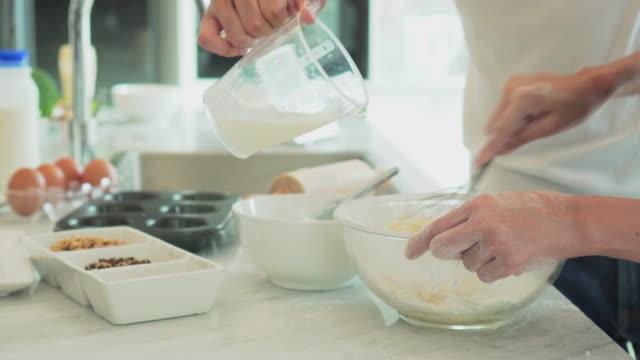 vídeos y material grabado en eventos de stock de pareja joven prepara la masa mezclando los ingredientes en el tazón de fuente, close-up - hornear