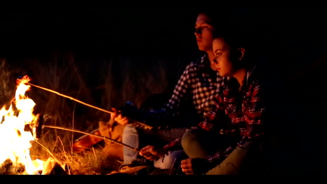 Young couple preparing meal on campfire