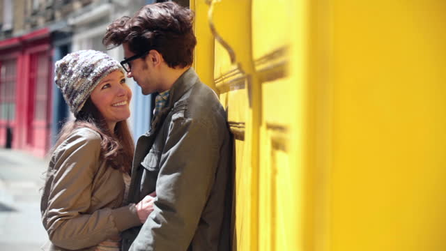 Young couple pull each other into an embrace on colorful London street corner.