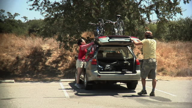 ws young couple pulling out parking lot / malibu creek, california, usa - beladen stock-videos und b-roll-filmmaterial