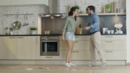 Young Couple Quarrels in the Kitchen. Girl Had Enough and She Breaks the Plate. Man Screams in Frustration and Angrily Gesticulates. Slow Motion.