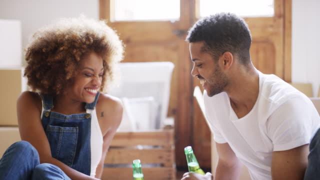 vídeos de stock, filmes e b-roll de pares novos que levantam o brinde com frascos de cerveja - brinde