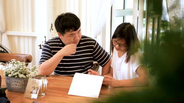 vídeos de stock, filmes e b-roll de menu de leitura do jovem casal no restaurante - lua de mel