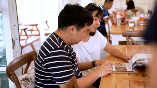 junges paar lesung menü im restaurant - gast stock-videos und b-roll-filmmaterial