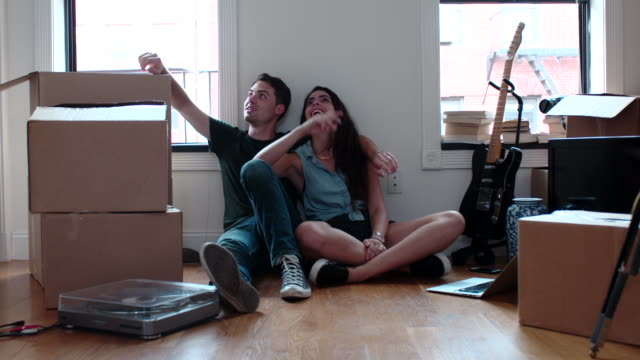 vídeos de stock e filmes b-roll de young couple  relax in new apartment - par