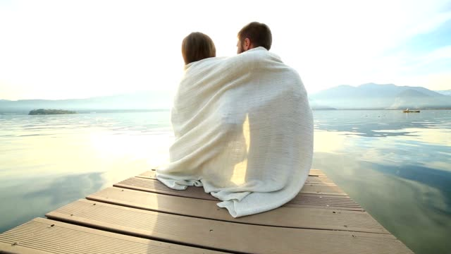young couple relaxes on lake pier, wrapped in blanket - blanket stock videos and b-roll footage