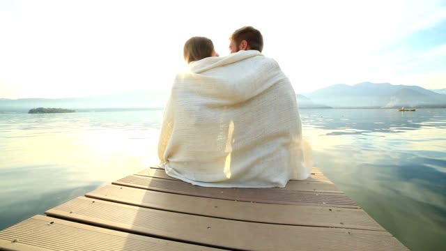 Young couple relaxes on lake pier, wrapped in blanket
