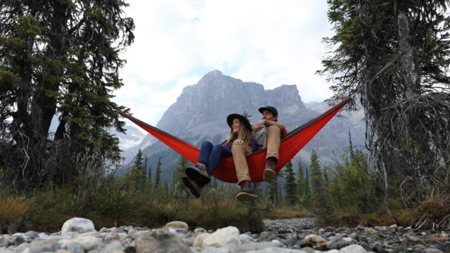 a young couple relaxing in a hammock surrounded by mountains. - kanada stock-videos und b-roll-filmmaterial