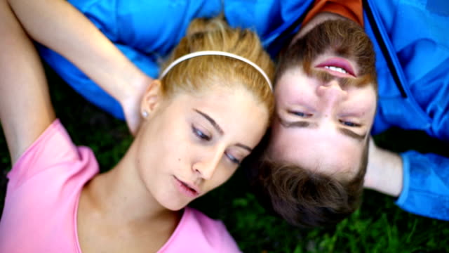 young couple relaxing in park. - lying down stock videos & royalty-free footage