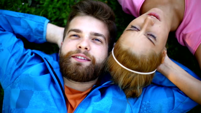 young couple relaxing in park. - pink shirt stock videos and b-roll footage