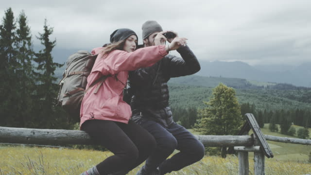 Young couple relaxing in the mountains. Using binoculars