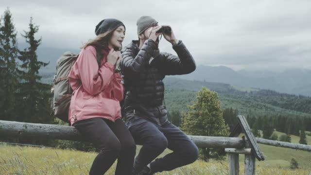 junges paar in den bergen entspannen. mit dem fernglas - fernglas stock-videos und b-roll-filmmaterial