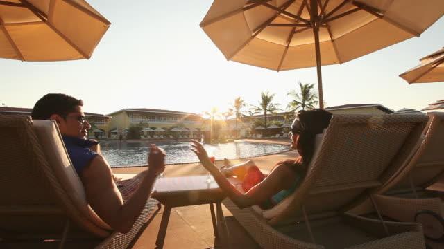 vídeos y material grabado en eventos de stock de young couple relaxing on a lounge chair in a resort - tumbona