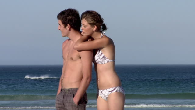 slo mo ms young couple relaxing on beach, cape town, south africa - halbbekleidet stock-videos und b-roll-filmmaterial