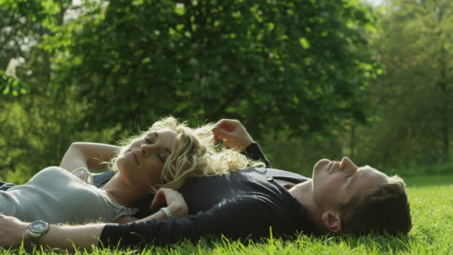 ms young couple relaxing on lawn in green park / london, uk - reclining stock videos & royalty-free footage