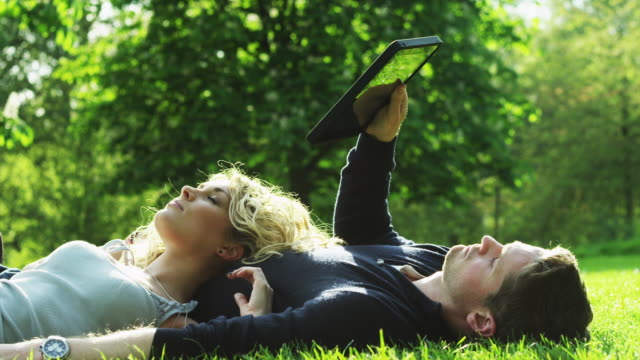 ms young couple relaxing on lawn in green park, man looking at tablet pc / london, uk - apple computers stock videos & royalty-free footage