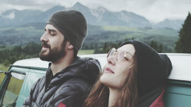 Young couple relaxing on the meadow. Leaning on the van