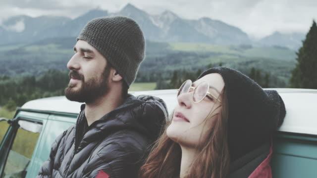 vídeos y material grabado en eventos de stock de joven pareja relajarse en el prado. apoyarse en la furgoneta - ojos cerrados