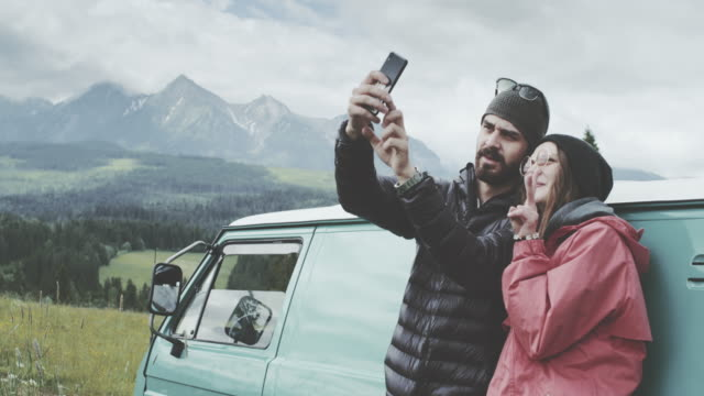 Young couple relaxing on the meadow. Making selfie