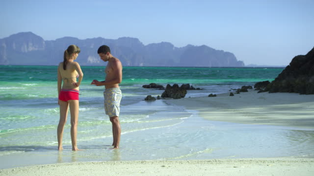 stockvideo's en b-roll-footage met ws young couple relaxing on tropical beach, krabi, thailand - zwembroek