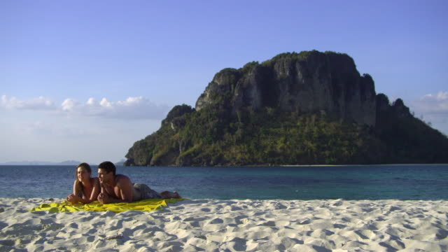 stockvideo's en b-roll-footage met ws pan young couple relaxing on tropical beach, krabi, thailand - zwembroek