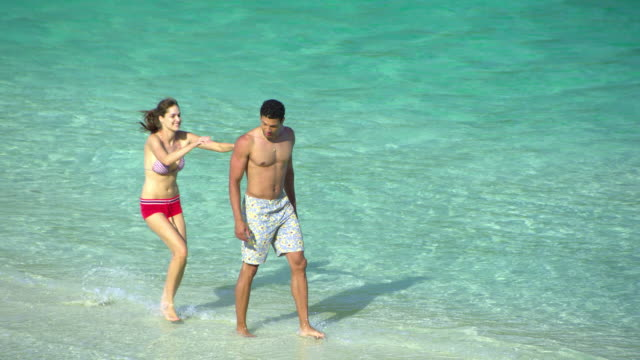 ws ha young couple relaxing on tropical beach, man giving piggy back riding to woman, krabi, thailand - see other clips from this shoot 1459 stock videos and b-roll footage