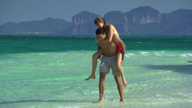 stockvideo's en b-roll-footage met ws pan young couple relaxing on tropical beach, man giving piggy back riding to woman, krabi, thailand - zwembroek