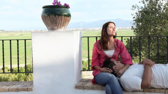 vídeos de stock e filmes b-roll de young couple relaxing with man on woman's lap - colo