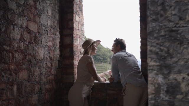 young couple resting at a castle wall opening - castle stock videos & royalty-free footage