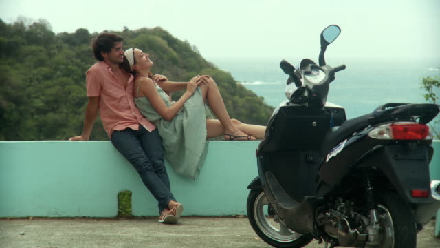 ms young couple resting on wall, sea in background / scarborough, tobago, trinidad and tobago   - legs crossed at ankle stock videos and b-roll footage