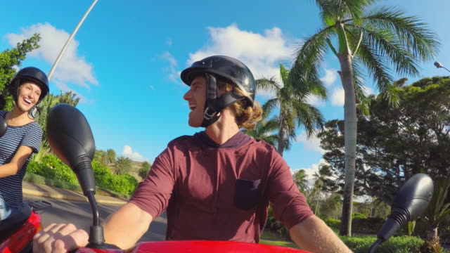 Young couple ride mopeds together in Hawaii