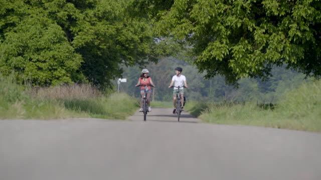 vídeos de stock, filmes e b-roll de jovem casal passeios de bicicletas, bate-papo e rir - jovem de espírito