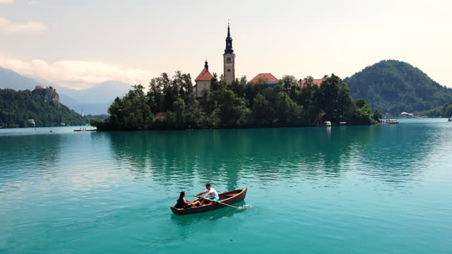 aerial young couple riding a rowing boat towards the lake island - lake bled stock videos & royalty-free footage