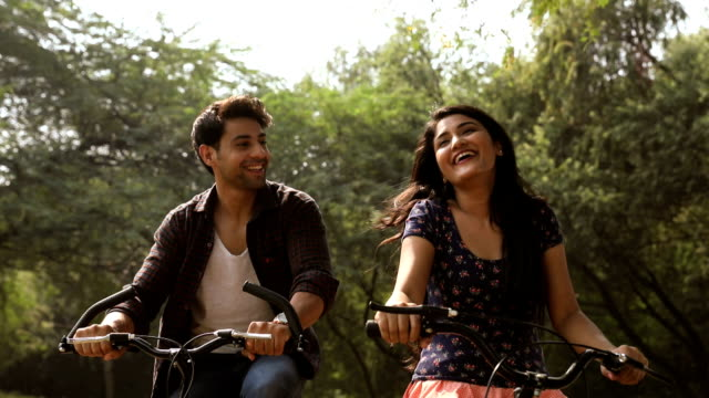 Young couple riding bicycle in the park, Delhi, India