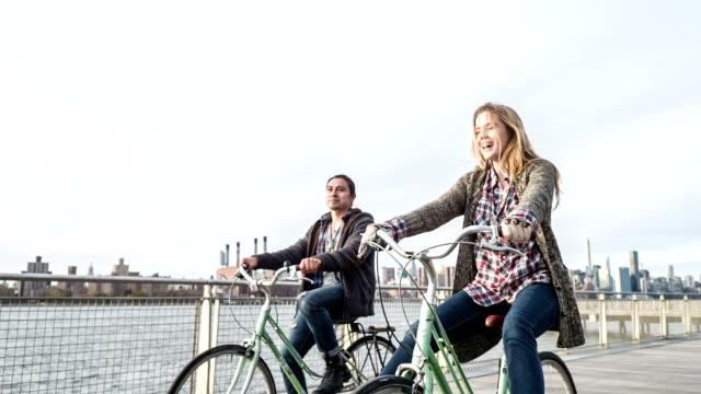 Jeune couple bicyclettes à cheval sur la promenade