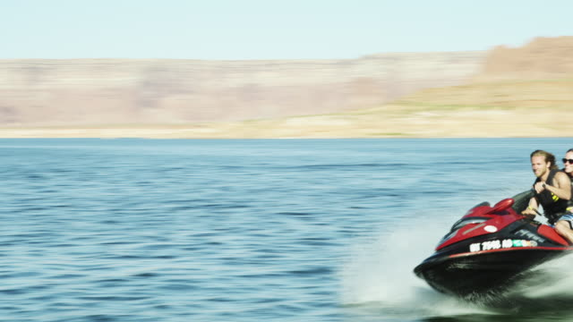 slo mo ws ts young couple riding jet boat in lake powell / utah, usa - lake powell stock videos and b-roll footage