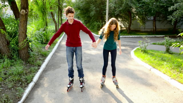 young couple riding on roller skates - blade stock videos & royalty-free footage