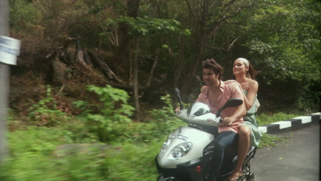 ws slo mo young couple riding on scooter / scarborough, tobago, trinidad and tobago   - moped stock videos and b-roll footage