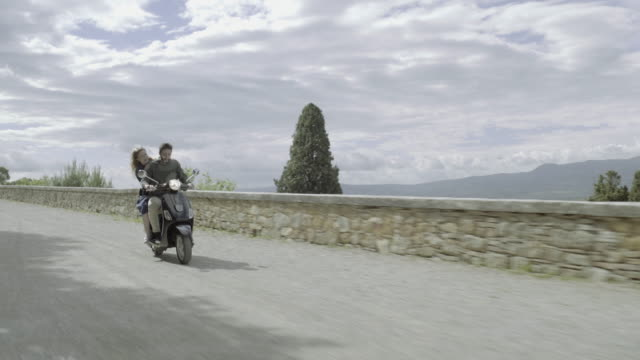 young couple riding on scooter - motorino video stock e b–roll