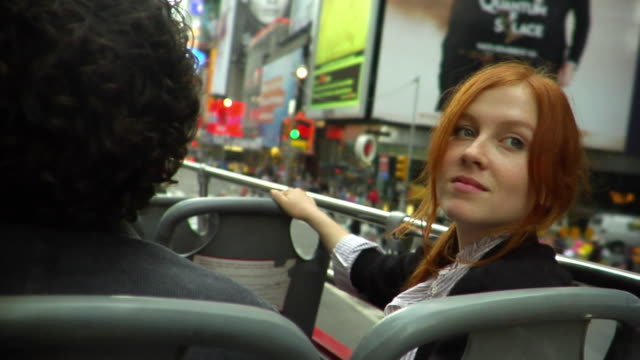 stockvideo's en b-roll-footage met cu young couple riding on the top level of a double decker tour bus through times square/ new york city - dubbeldekker bus