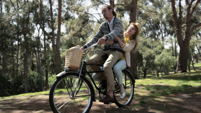 young couple riding one bicycle in forest - behind stock videos & royalty-free footage