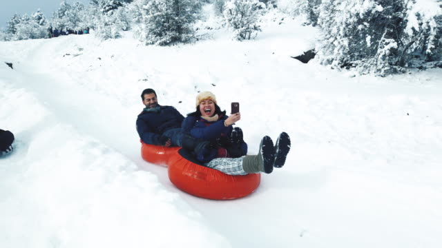 young couple riding tubes on snowy hill in winter - winter coat stock videos & royalty-free footage