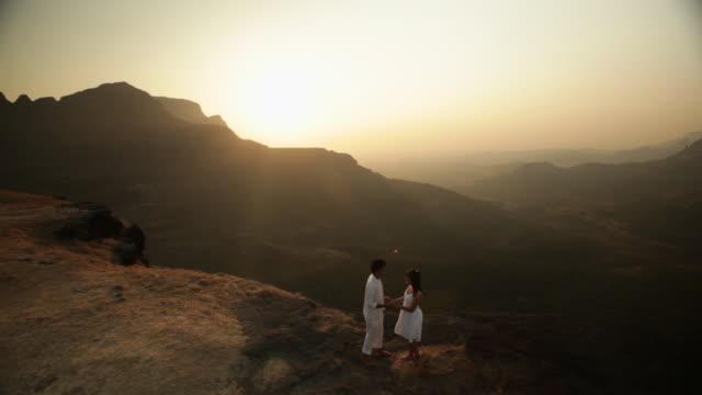 vídeos de stock e filmes b-roll de young couple romancing on a cliff of a mountain  - chaleira de chá