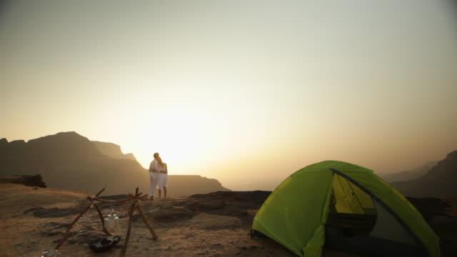 vidéos et rushes de young couple romancing on a cliff of a mountain  - tente